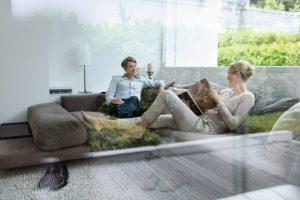 Vista di un salotto con una coppia che si rilassa sui divani da una vetrata Schüco-antieffrazione